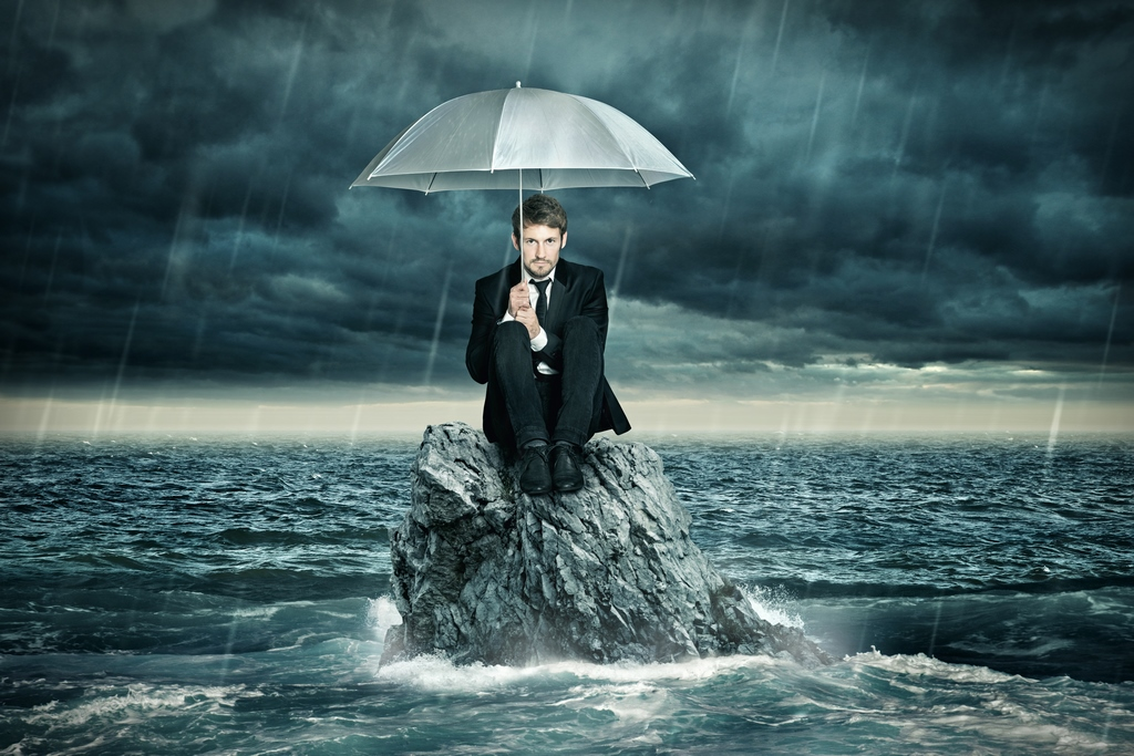 businessman-under-umbrella-in-the-ocean